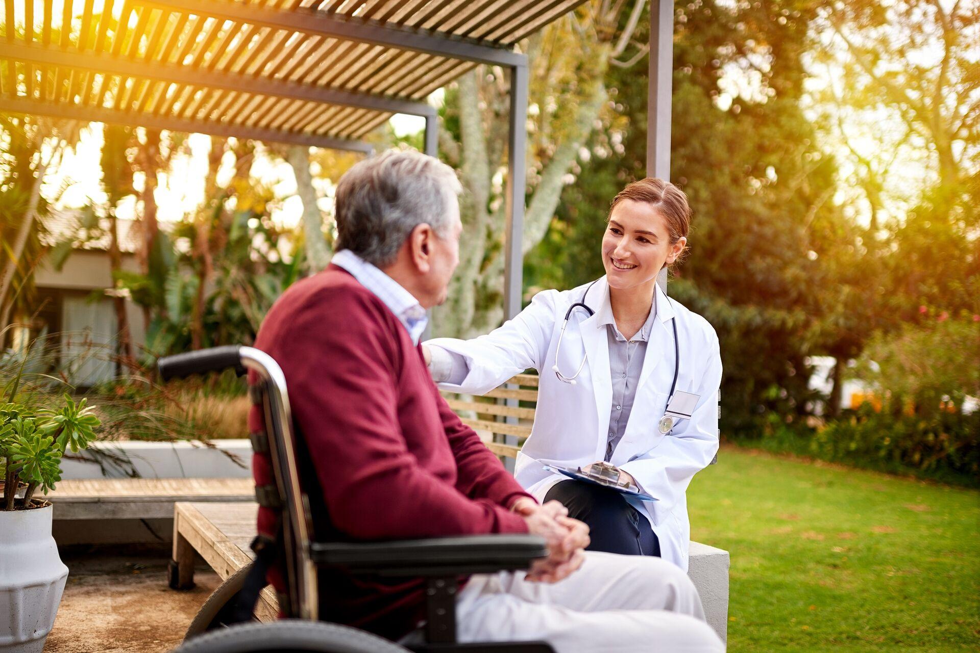senior man in a wheelchair talking with a caregiver