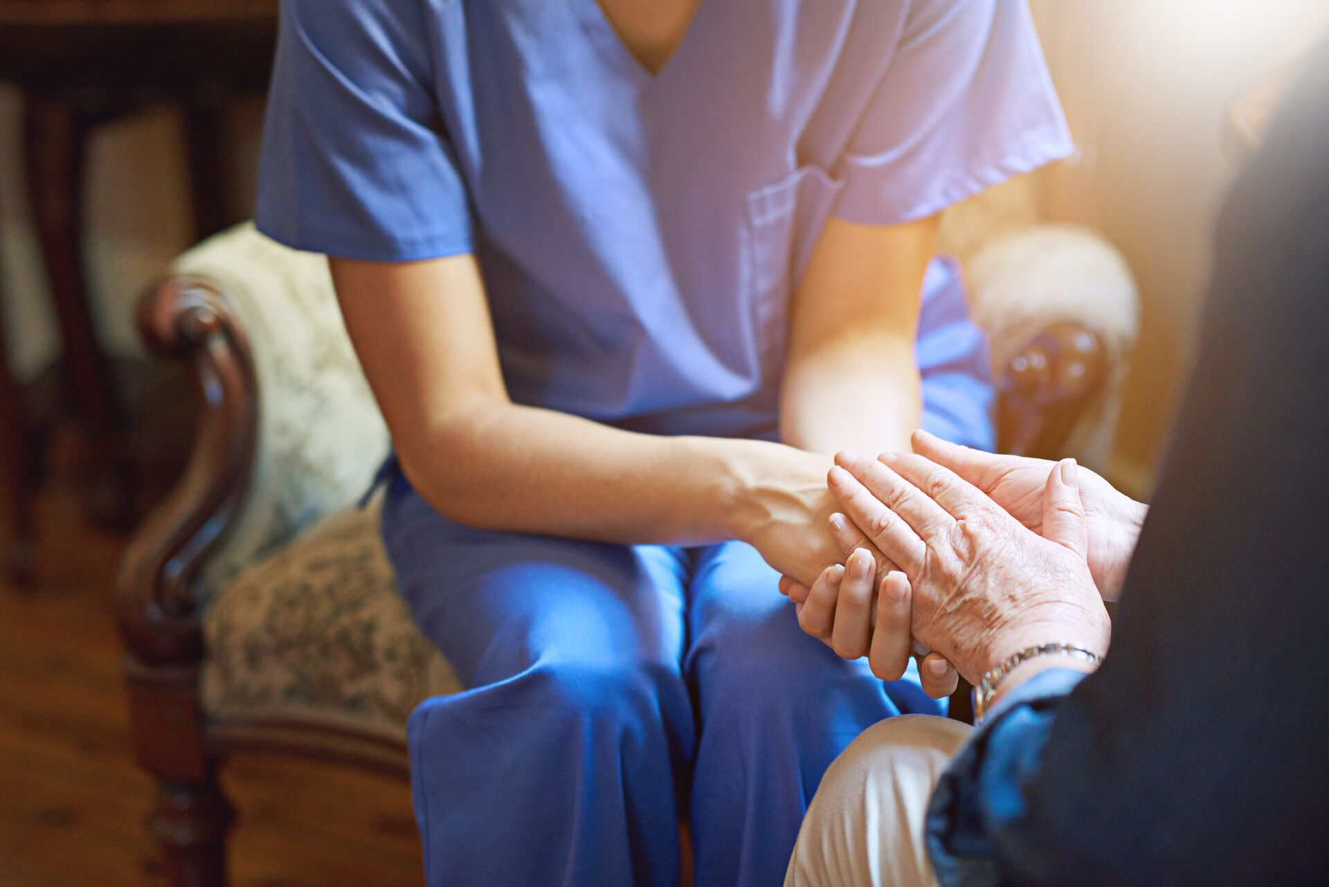 senior and healthcare worker hand in hand
