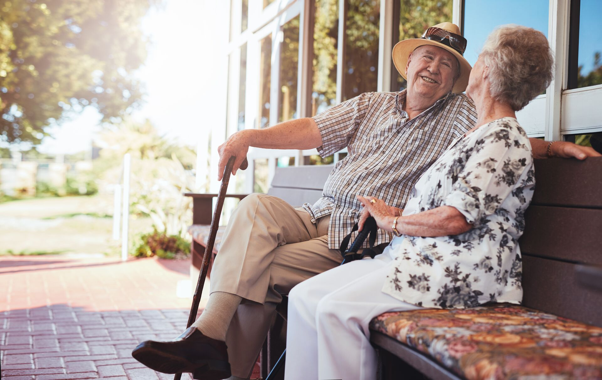 seniors talking while sitting on a bench outside an assisted living facility