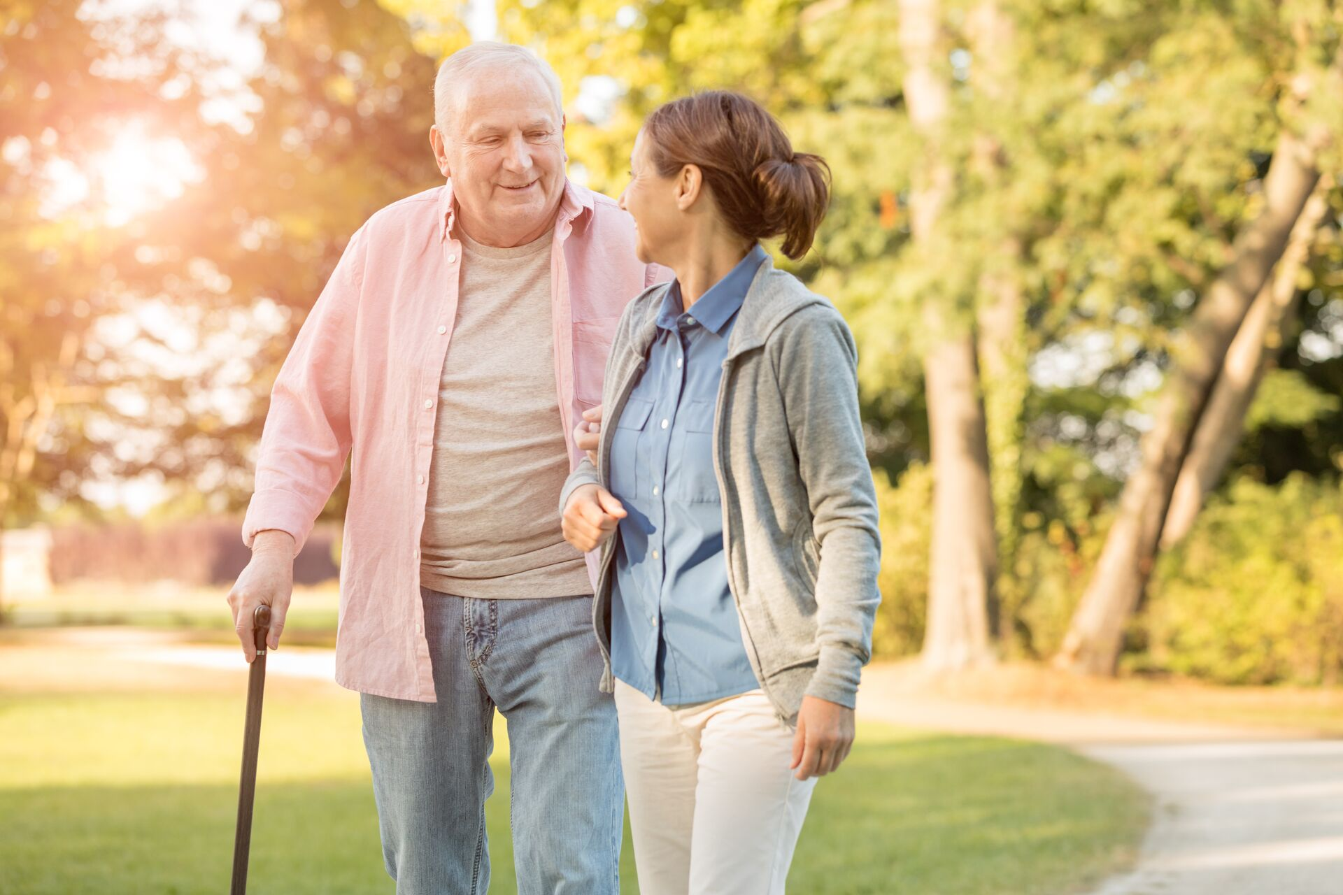 senior walking outside with a cane and with a younger adult woman