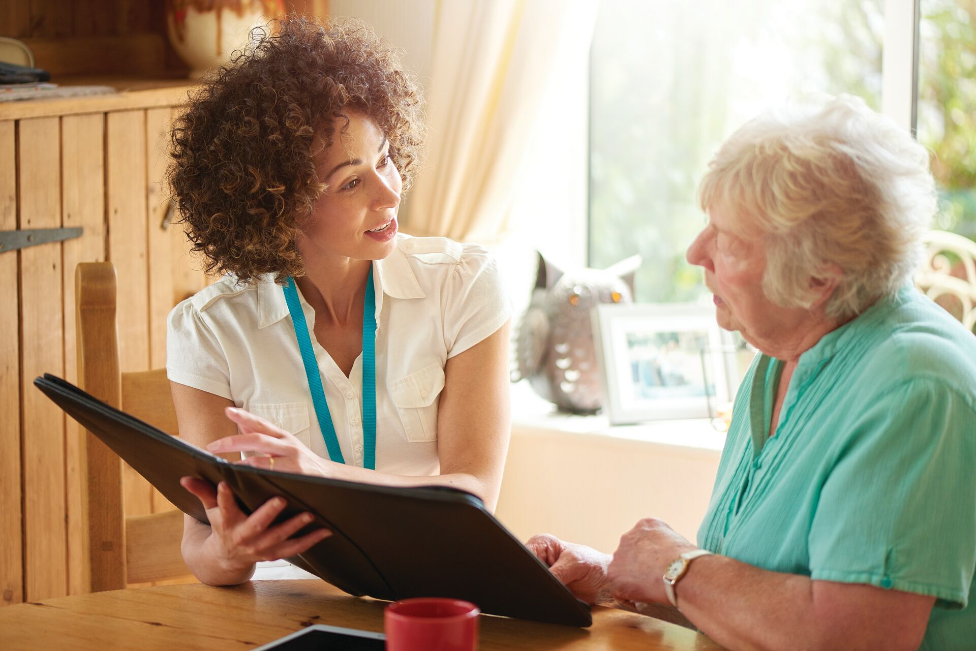senior looking at a binder with a caregiver