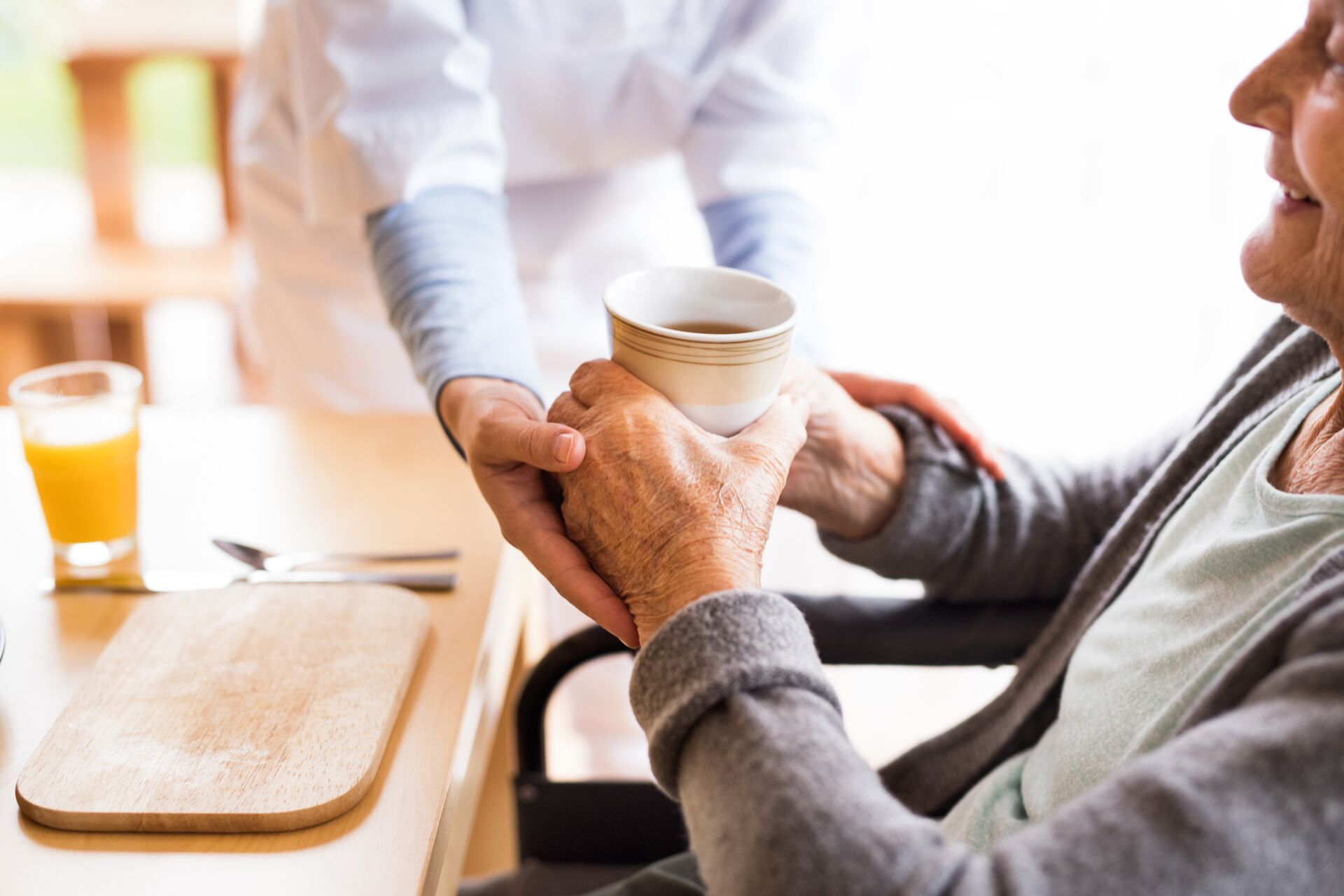 senior in assisted living getting help with holding a cup of coffee