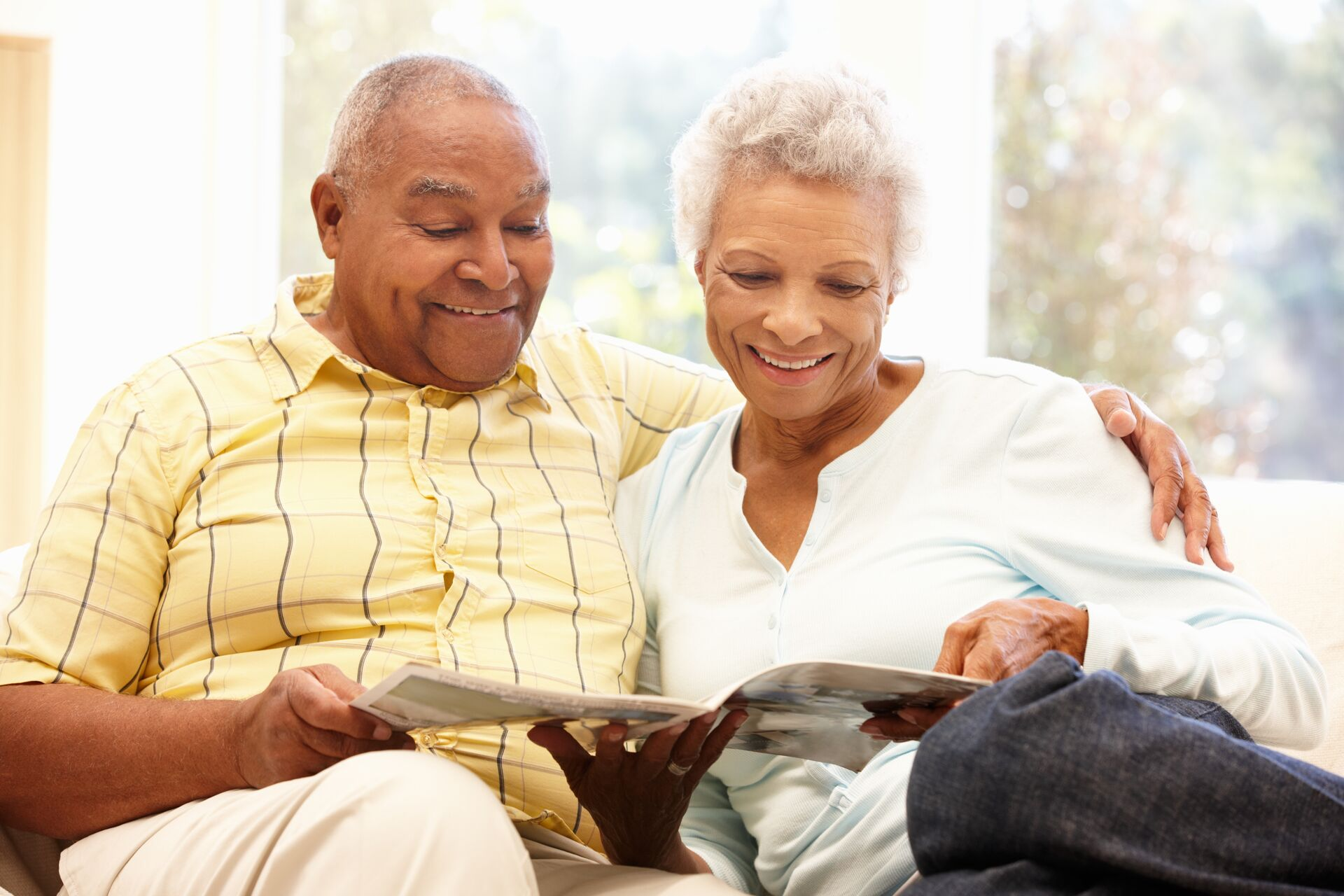 senior couple looking at a magazine together in their senior apartment