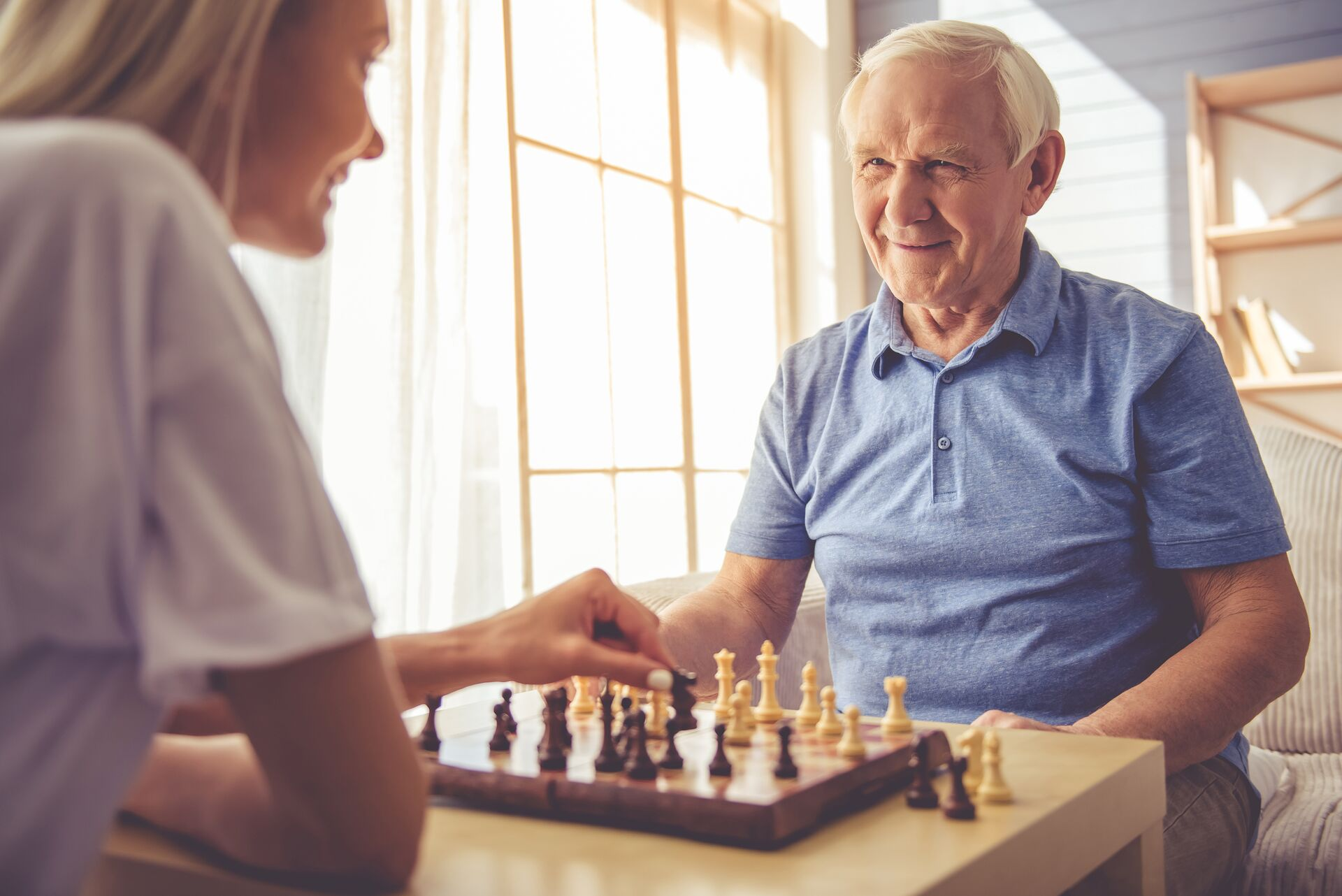 senior living resident playing chess with an adult woman