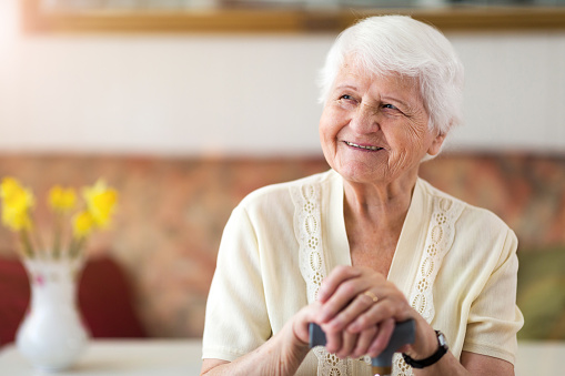 senior lady smiling while resting her hands on a walking cane