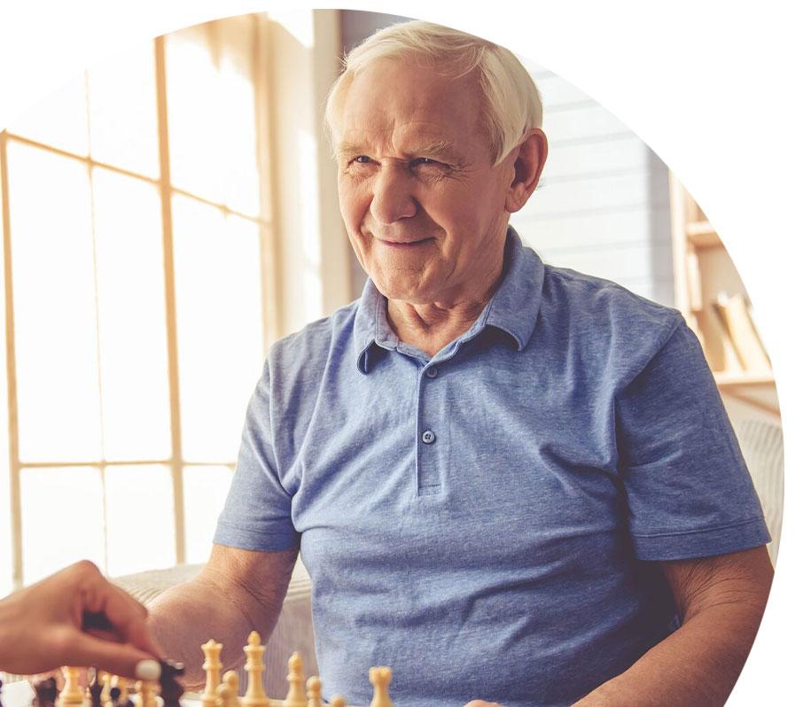 senior man playing chess while smiling